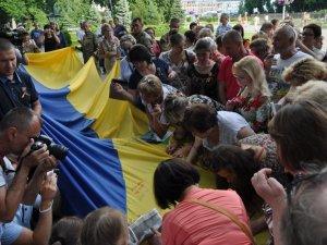Фото: Полтавські волонтери підписали десятиметровий український прапор